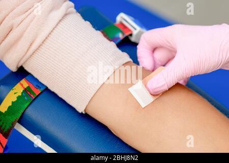 Die Krankenschwester Hand klebt nach der Blutentnahme einen Klebstoff-Putz auf den Arm, - Stockfoto