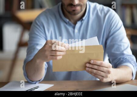 Fokussierter Geschäftsmann liest Brief, hält Umschlag in den Händen nah an - Stockfoto