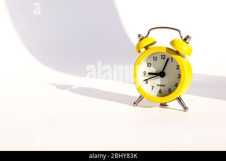 Gelber Wecker mit großem Schatten auf weißem Hintergrund, Kopierbereich - Stockfoto