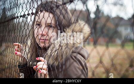 Hübsches junges Mädchen, das den Zaun hält, traurig, depressive Stimmung sieht und Emotionen markiert - Stockfoto