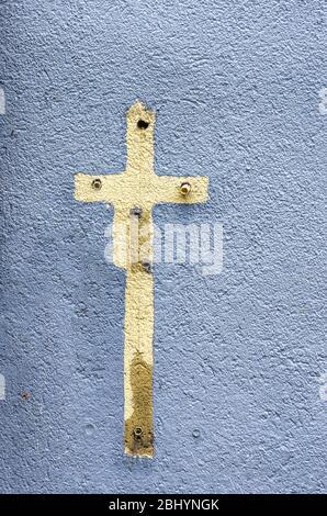 Aufdruck eines Kreuzschildes mit Farbe auf einer Hauswand voller alter Ausdehnungsdübel umgeben. - Stockfoto