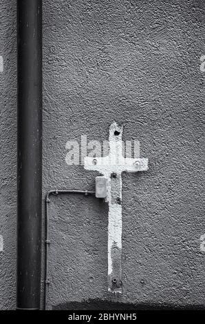 Aufdruck eines mit Farbe umgebenen Kreuzschildes auf einer Hauswand voller alter Ausdehnungsdübel mit Stromanschluss. - Stockfoto