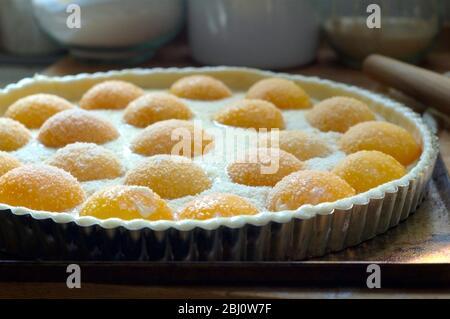 Herstellung Pfirsichtart mit halbierten Pfirsichen und Creme Patissiere auf Blätterteig in Metalldose, bestreut mit Gießzucker und gemahlenen Mandeln. - - Stockfoto