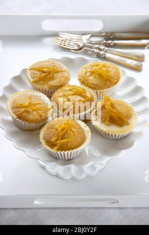 Zitronenmuffins mit Zitronenschale auf weißem Cakestand glasiert - - Stockfoto