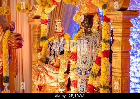 Das Idol von Herrn Balaji und Lakshmi, das mit Verzierungen und Blumen an einer südindischen hinduistischen Hochzeit verziert wird - Stockfoto