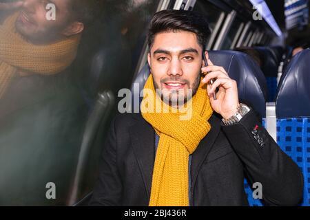 Geschäftsmann pendelt mit dem Telefon im Zug zur Arbeit - Stockfoto