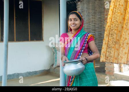Indische Frau in Sari bei ihrem Haus im Dorf - Stockfoto