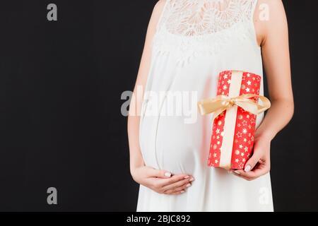 Nahaufnahme Porträt der schwangeren Frau in weißem Kleid mit einem Geschenk-Box auf schwarzem Hintergrund. Schwangerschaftsfeier. Kopierbereich. - Stockfoto