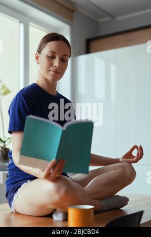 Junge Frau in Yoga-Posen entspannen Lesen, sitzen auf einem Holztisch in einem modernen Interieur mit Fenstern im Hintergrund