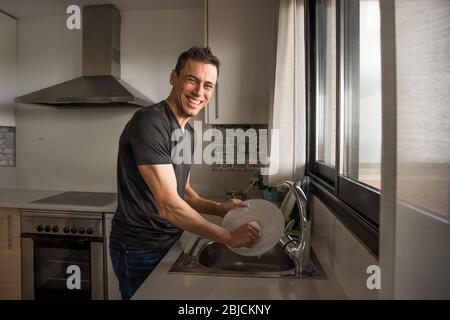 Lächelnder und glücklicher Mann, der in der Küche neben einem Fenster Geschirr spülte. Mittlere Aufnahme. - Stockfoto