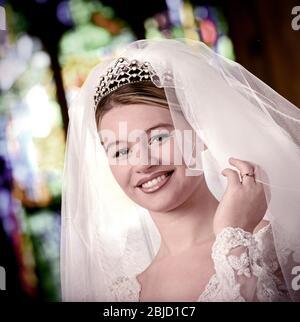 Braut in der Kirche, traditionelle 1990 's weißen Hochzeit Brautkleid Schleier und Tiara trägt einen Ehering lächelt an Kamera in der Kirche mit Glasfenster hinter retro 1995 Hochzeit Braut Mode Stil Porträt - Stockfoto