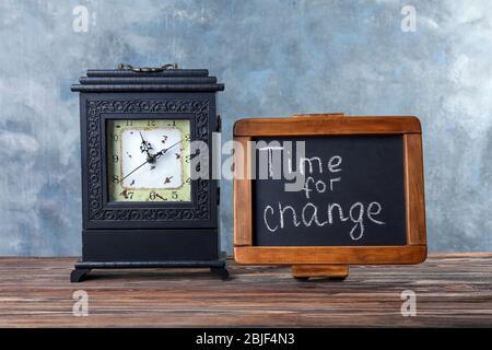 Tafel mit Text ZEIT FÜR VERÄNDERUNG und Retro-Uhr auf Holztisch - Stockfoto
