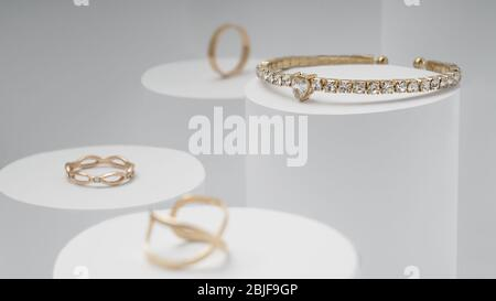 Goldenes Armband mit Diamanten und goldenen Ringen auf weißem Display - Stockfoto