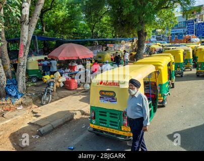 Neu Delhi / Indien - 27. September 2019: Sikh-Mann vor Tuk Tuks auf der Straße in Neu Delhi, Indien. Tuk Tuks sind mit I Love Kejriwal Slo gemalt - Stockfoto