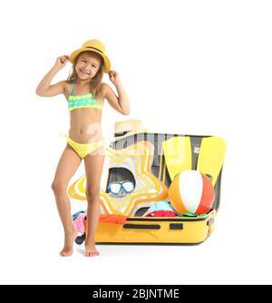 Liebenswert kleines Mädchen in Badeanzug in der Nähe von Koffer auf weißem Hintergrund - Stockfoto