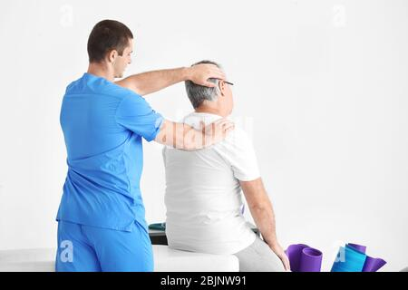 Physiotherapeut in der modernen Klinik mit Senior Patient - Stockfoto