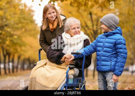 Nette Kinder mit ihrer älteren Großmutter im Rollstuhl im Freien am Herbsttag - Stockfoto