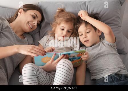 Mutter liest Schlafenszeit Geschichte zu Kindern zu Hause - Stockfoto