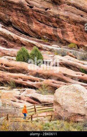 Eine Person geht mit einem Hund in der Nähe des Red Rocks Amphitheatre etwas außerhalb von Denver, Colorado, USA. - Stockfoto