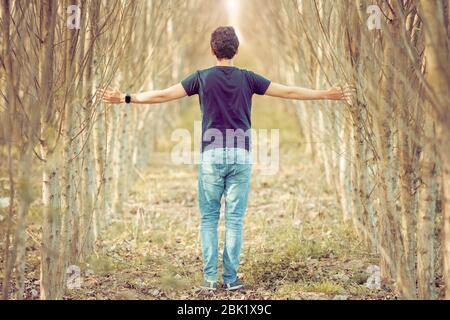 Junger Mann auf einem Spaziergang durch die Natur, ausgewogene Gedanken und Entspannung
