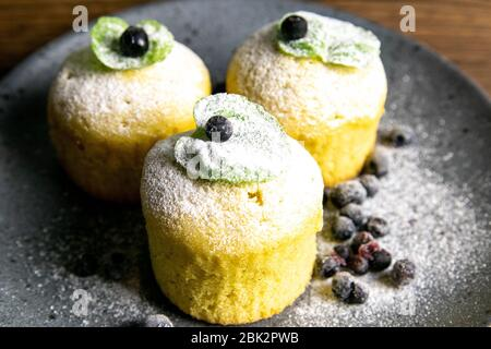Heidelbeer-Muffins mit Zitrone und Minze auf grauem Teller auf dunklem Holztisch. Vorderansicht, Nahaufnahme - Stockfoto
