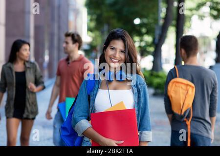 Schöne kaukasische junge Erwachsene Frau zu Fuß in der Stadt mit einer Gruppe von Studenten im Freien in der Stadt - Stockfoto