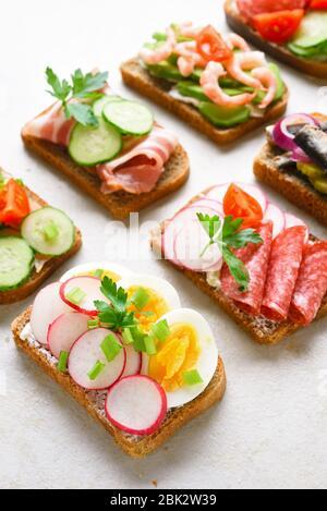 Auswahl offener Sandwiches auf hellem Steingrund. Leckerer gesunder Snack. Nahaufnahme