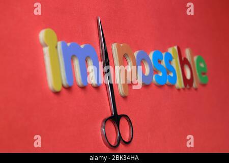 Selbstglaube und positives Konzept, Schere schneiden das Wort unmöglich zu lesen möglich. Vom Unmöglichen zum Möglichen. - Stockfoto