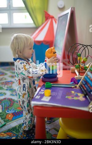 Blonde Junge spielt mit Spielzeug im Kinderspielzimmer. Stockfoto