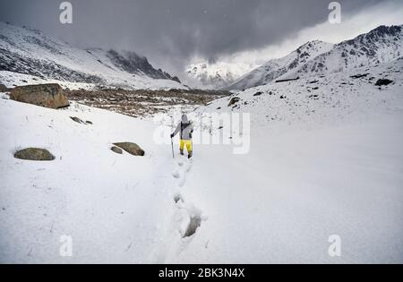 Touristische im Schnee weg zu schönen bewölkten Himmel Hintergrund. Outdoor klettern Konzept.
