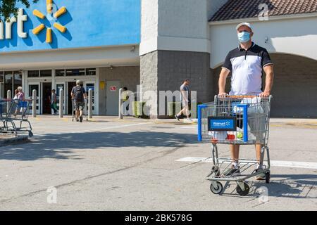 Mann trägt medizinische Maske auf Walmart Parkfläche. Quarantäne wegen Coronavirus Zeit. - Stockfoto