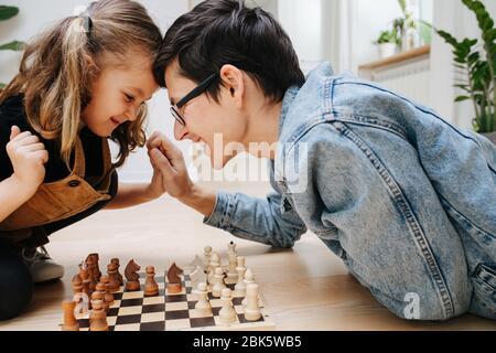 Freundliches Wettkampfkonzept. Papa und dau spielen Schach und Schlagköpfe
