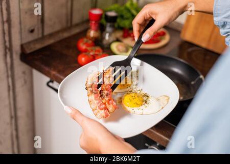 Hände von jungen Frauen, die gebratenen Speck und Eier auf den Teller legen, während sie in der Küche beim Elektroherd stehen und frühstücken gehen