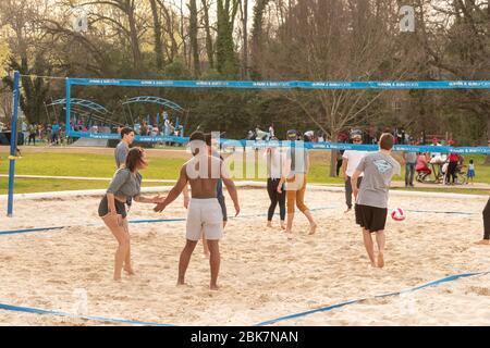Charlotte, NC/USA - 24. März 2019: Mitnehmer-Volleyball-Spiel im Freedom Park auf einem Sandplatz mit hellblauem Netz, Gras und Bäumen. - Stockfoto