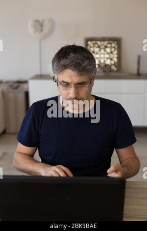 Vertikales Porträt eines Mannes mittleren Alters mit Brille, der von zu Hause aus mit schwarzem Laptop arbeitet. - Stockfoto