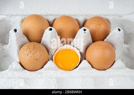 Frische rohe Hühnereier in einem Papierkarton. Ein Ei ist halb gebrochen und enthält ein Eigelb. Nahaufnahme, Ansicht von oben.