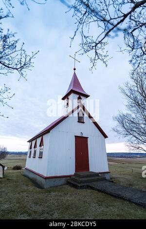 Typische rote Holzkirche in Fludir Stadt im Süden Islands innerhalb des Goldenen Kreises. Sonnenuntergang Licht Stock Bild