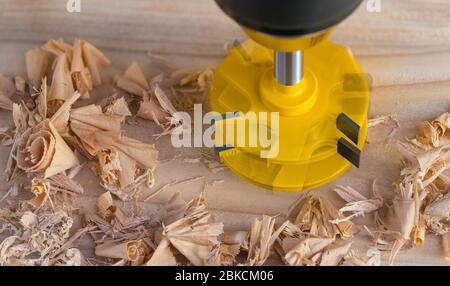 Rotierender Kopierfräser auf Holzplanke und verstreute gewellte Späne. Gelber Schaftfräser und präzise scharfe Kanten. Holztechnologie. - Stockfoto