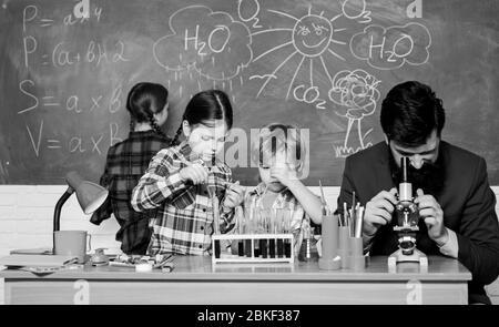 Faszinierende Chemie Lektion. Man bärtige Lehrer und Schüler mit Reagenzgläsern im Klassenzimmer. Beobachten Sie die Reaktion. Wissenschaft ist immer die Lösung. Schule Chemie Experiment. Erklären der Chemie zu Kindern. - Stockfoto