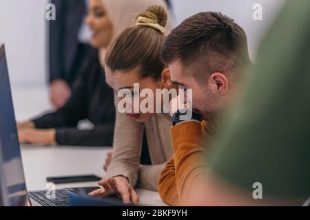 Junge Geschäftskollegen arbeiten in einer komfortablen Büroatmosphäre an einem Computer zusammen. - Stockfoto