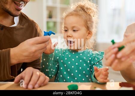 Horizontale mittlere Nahaufnahme von jungen Vater demonstriert blauen spielen Teigform zu seiner fröhlichen kleinen Tochter