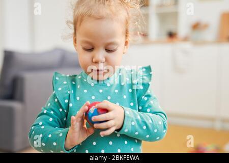 Kleine kaukasische Mädchen trägt türkisfarbenen Tupfen Kleidung machen bunte Modellierung Tonball, horizontale Porträt geschossen