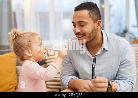 Fröhliches kleines Mädchen mit Spaß malen bunte Striche auf Gesicht ihres glücklichen jungen Vaters - Stockfoto