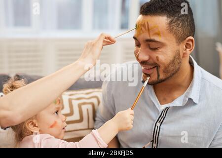 Junge Frau und kleines Mädchen mit Spaß malen bunte Gouache Striche auf Gesicht der glücklichen jungen Mann - Stockfoto