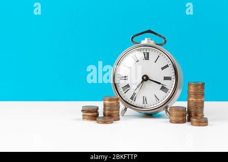 Wecker und Geldmünzen auf dem Tisch.