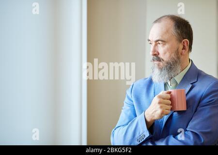 Stilvoller Senior-Mann mit Bart auf dem Gesicht trägt blauen Anzug hält Tasse Kaffee Blick aus dem Fenster, Kopie Raum - Stockfoto