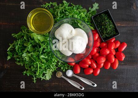 Rucola mit langsam gerösteten Tomaten und Burrata: Zutaten für eine andere Art des klassischen Caprese-Salats aus Traubentomaten, Rucola, Basilikum
