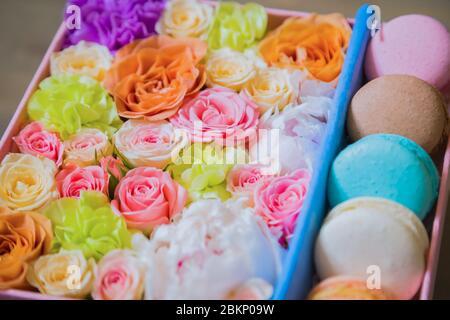 Nahaufnahme der Geschenkbox mit Blumen und bunten Makronen im Blumenladen. Floristik, handgefertigt, Hochzeit, Geburtstag, Dessert, Keks, süße Speisen und - Stockfoto