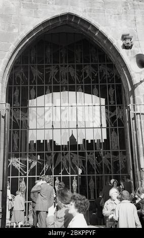 """1961, historisches Bild der neuen Kathedrale, Coventry, England, mit einem der neu gestalteten Fenster. Im Mai 1962 wurde ein neues """"modernistisches"""" Gebäude offiziell auf dem Gelände der Ruinen der alten Kathedrale eröffnet. Das Gebäude wurde von Basil Spence im radikalen 'Brutalist'-Architekturstil entworfen, der in dieser Zeit üblich ist. - Stockfoto"""