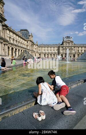 Kinder spielen am Brunnen Pool im Napoleon Hof des Louvre Museum.Paris.Frankreich - Stockfoto